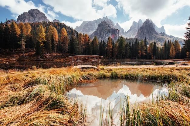 Niesamowity widok na majestatyczne góry z lasami przed nimi w jesienny dzień. kałuża wychodząca z jeziora z małym mostkiem pośrodku