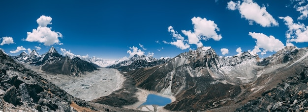 Niesamowity widok panoramiczny na potężne himalaje i spokojne jezioro gokyo na niebieskim tle pochmurnego nieba. trekking everest base camp w parku narodowym sagarmatha w północno-wschodnim nepalu.