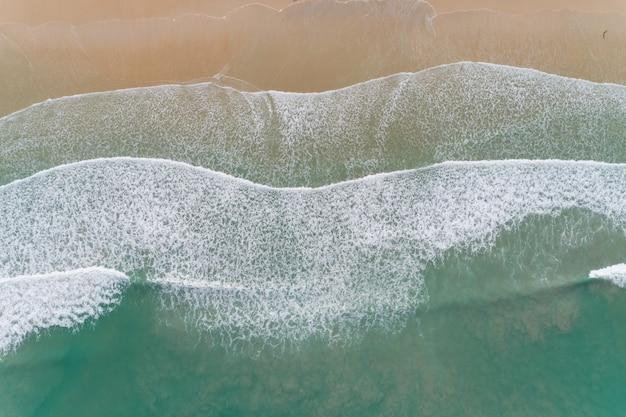 Niesamowity widok widok z lotu ptaka z kamery drona, zdjęcie fal rozbijających się na piaszczystym brzegu, widok z góry na piękną piaszczystą plażę o porannym wschodzie słońca.