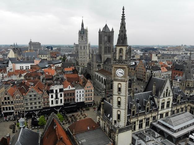 Niesamowity widok z góry. małe i wygodne miasteczko gent. średniowieczna historia wokół ciebie - musisz zobaczyć wszystkich odkrywców. widok z drona. z belgii z miłością. wieża zegarowa.