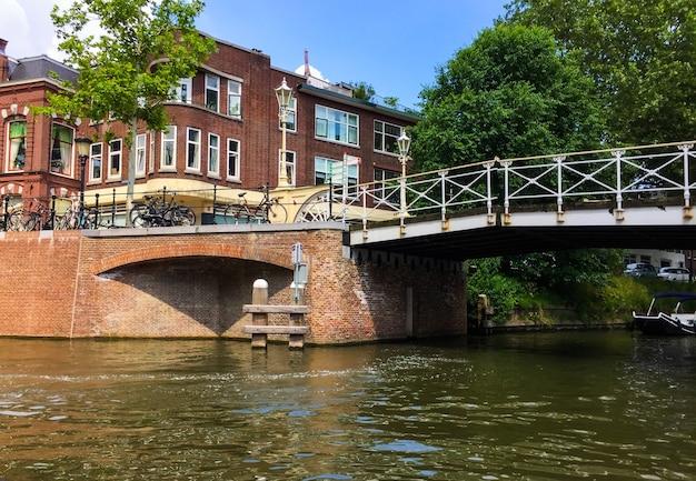 Niesamowity widok z łodzi turystycznej na jeden z mostów starego kanału oudegracht i piękne budynki