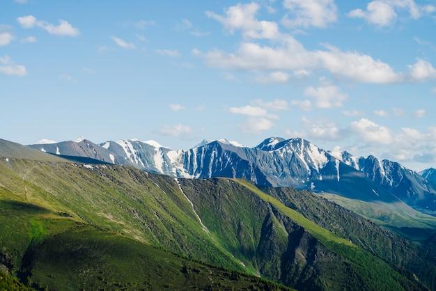 Niesamowity widok z lotu ptaka na duże ośnieżone góry skaliste i wielki lodowiec pod niebieskim niebem. cudowna żywa góralska sceneria z gigantycznymi górami ze śniegiem. piękny krajobraz alpejski z lodowcowymi górami.