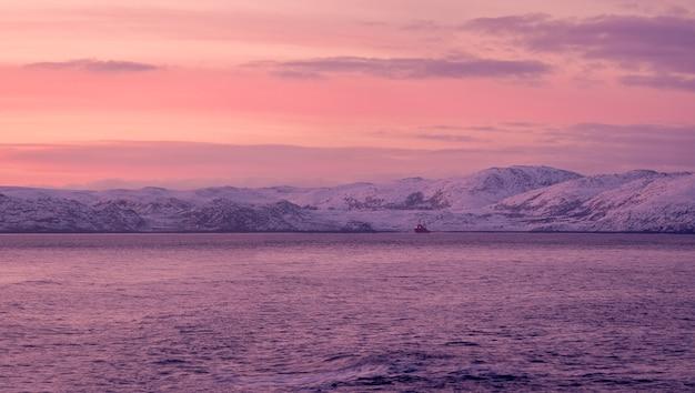 Niesamowity wschód słońca krajobraz polarny z białym śnieżnym pasmem górskim na horyzoncie