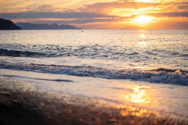 Niesamowity wschód słońca nad tropikalną plażą. żółte słońce nad morzem. fale w kolorze pomarańczowym. tle przyrody. piękna spokojna scena. poranek. światło słoneczne odbija się na powierzchni wody