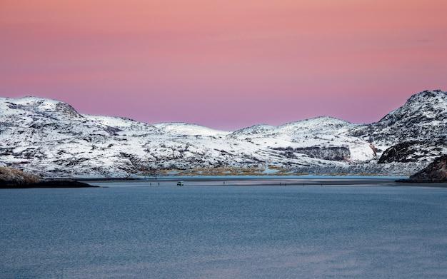 Niesamowity wschód słońca polarny krajobraz z białym śnieżnym pasmem górskim na horyzoncie. autobus turystyczny na przesmyku. panoramiczny widok na ocean arktyczny.
