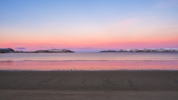 Niesamowity wschód słońca polarny krajobraz z białym śnieżnym pasmem górskim na horyzoncie. panoramiczny widok na ocean arktyczny. teriberka.