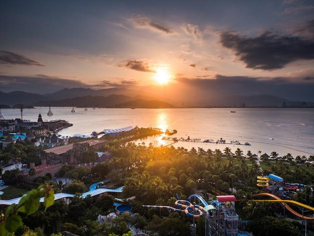 Niesamowity zachód słońca w parku rozrywki na morzu. markotny niebo z górami