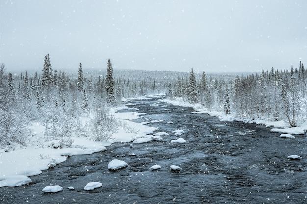 Niesamowity Zimowy Krajobraz Z Rzeką Wśród Zaśnieżonych Wzgórz Porośniętych Lasem Iglastym. Premium Zdjęcia