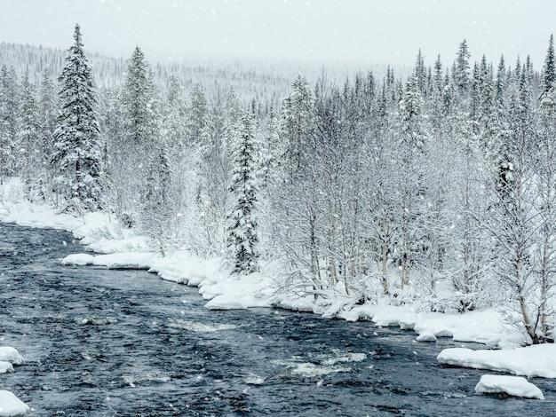 Niesamowity zimowy krajobraz z rzeką wśród zaśnieżonych wzgórz porośniętych lasem iglastym.