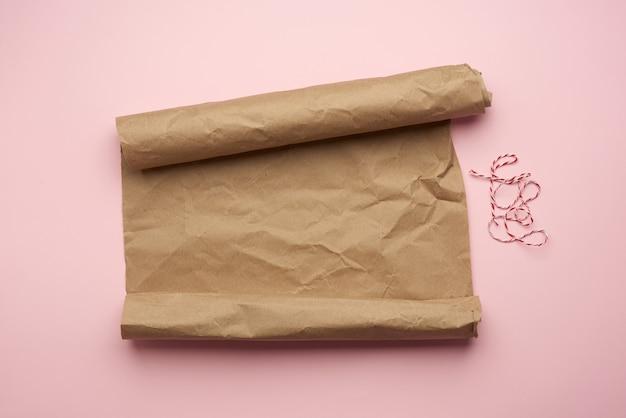 Nieskręcona rolka brązowego papieru na różowym tle, widok z góry