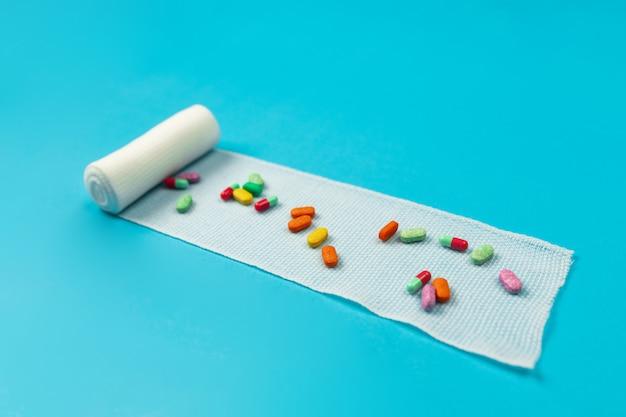 Nieskręcony biały bandaż z gazy, na którym leżą różne pigułki i pigułki na niebiesko. zdrowie. farmakologia.