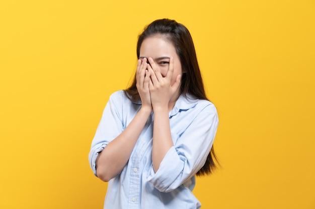 Nieśmiała azjatykcia kobieta w przypadkowej sukni zakrywa twarz i zerkanie