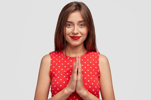 Nieśmiała brunetka młoda kobieta pozuje na białej ścianie