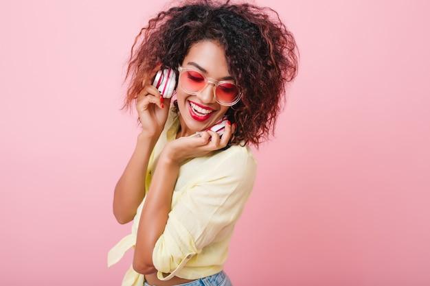 Nieśmiała czarna kobieta o lśniącej skórze, śmiejąca się przy dobrej muzyce. urocza mulatowa dziewczyna z stylowym makijażem relaksujący w słuchawkach.