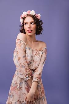 Nieśmiała europejska dama w romantycznej sukience rozgląda się. dobrze ubrana kręcona dziewczyna z kwiatami na głowie pozuje.