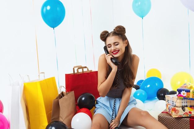 Nieśmiała i ładna dziewczyna siedzi z prezentami urodzinowymi i otrzymuje życzenia