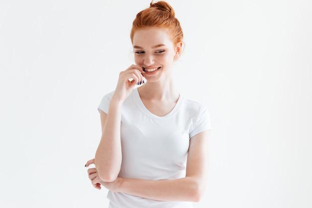 Nieśmiała imbirowa kobieta w koszulce patrzeje w dół