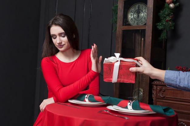 Nieśmiała kobieta odmawia przyjęcia prezentu w restauracji. związek pary