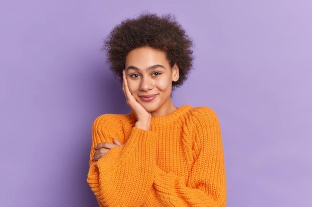 Nieśmiała ładna nastolatka z kręconymi włosami trzyma rękę na policzku, uśmiecha się delikatnie będąc w dobrym nastroju, nosi swobodny sweter z dzianiny.