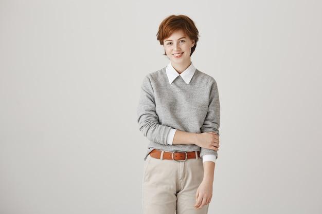 Nieśmiała ładna ruda dziewczyna z krótką fryzurą, pozowanie na białej ścianie