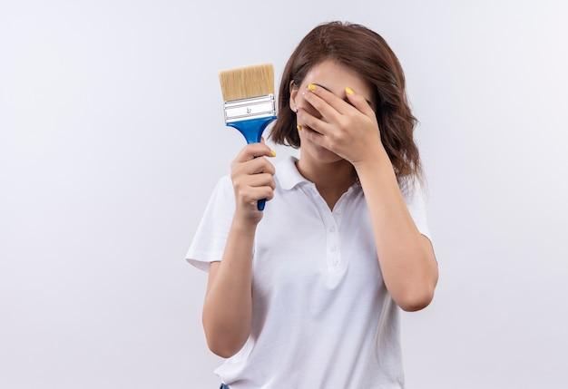 Nieśmiała młoda dziewczyna z krótkimi włosami, ubrana w białą koszulkę polo, trzymając pędzel zakrywający oczy ręką