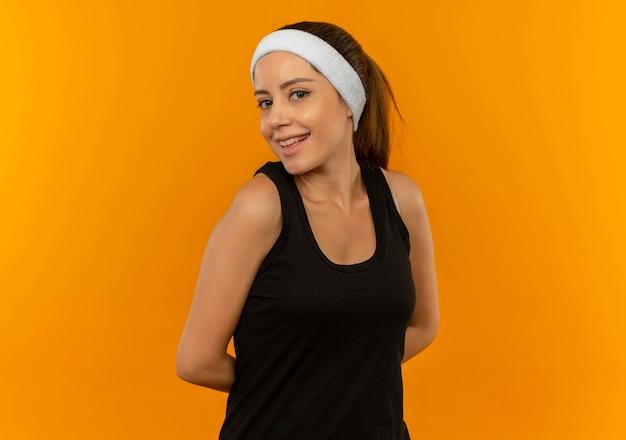 Nieśmiała młoda kobieta fitness w odzieży sportowej z opaską z uśmiechem na twarzy stojącej nad pomarańczową ścianą