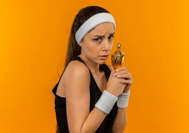 Nieśmiała młoda kobieta fitness w odzieży sportowej z pałąkiem na głowę trzyma trofeum z wyrazem strachu stojąc nad pomarańczową ścianą