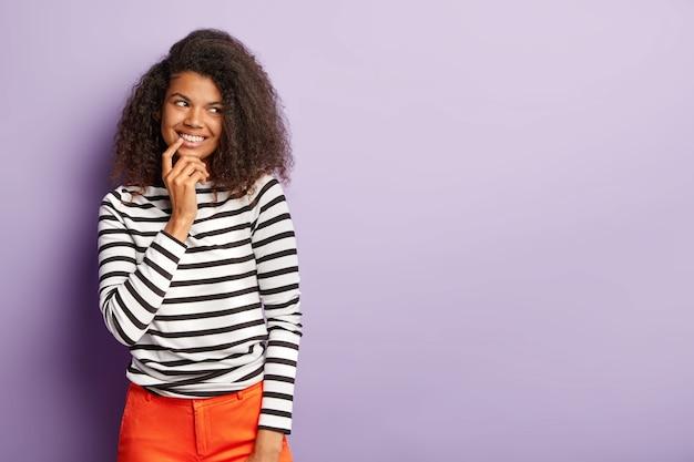 Nieśmiała optymistka o delikatnym, przyjaznym spojrzeniu, fryzura afro