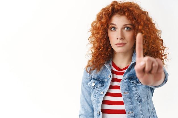 Nieśmiała, poważnie wyglądająca ruda ładna dziewczyna zbiera odwagę przedłużyć palec wskazujący tabu gest zakazu chętnych zająć minutę, uciszając zabronić działać nierozsądnie stojąc biała ściana