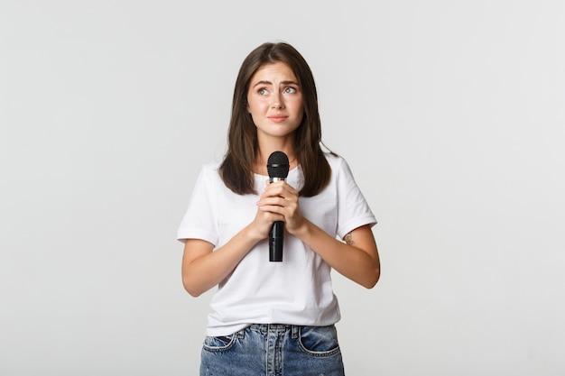 Nieśmiała śliczna brunetka dziewczyna, która boi się śpiewać publicznie, stoi z mikrofonem i wygląda na zdenerwowaną.