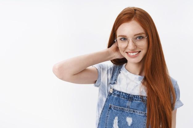 Nieśmiała śliczna rudowłosa studentka długie naturalne rude włosy niebieskie oczy, dotyk szyi skromny uśmiech, rumieniąc się zalotna rozmowa, stoisko biała ściana wesoły entuzjastyczny nastrój