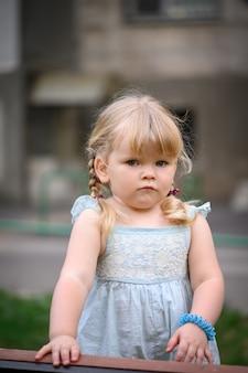 Nieśmiała smutna mała blond dziewczynka z dwoma warkoczykami na tle miejskiego lata