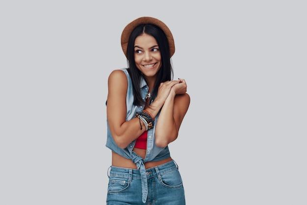 Nieśmiała, stylowa młoda kobieta odwracająca wzrok i uśmiechnięta stojąc na szarym tle