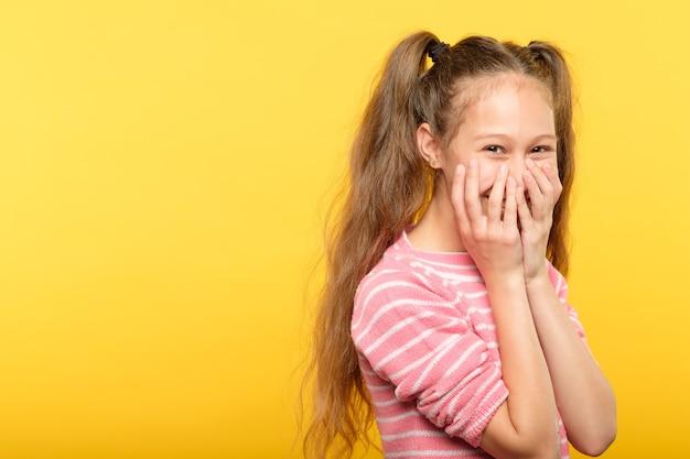 Nieśmiała uśmiechnięta zakłopotana dziewczyna zakrywająca usta rękami. młody ładny dziecko emocjonalny portret na żółto.