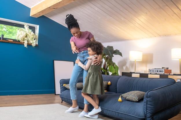 Nieśmiałość. afroamerykanka młoda matka wskazująca dłoń do przodu, by przytulić nieśmiałą córeczkę stojącą w pokoju w domu