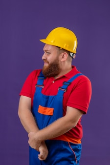 Nieśmiały młody brodaty mężczyzna budowniczy w mundurze budowy i hełmie ochronnym, trzymając się za ręce razem, patrząc na bok na fioletowym tle
