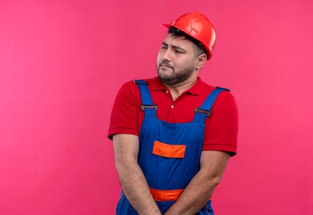 Nieśmiały młody budowniczy mężczyzna w mundurze budowlanym i hełmie ochronnym, trzymając się za ręce razem