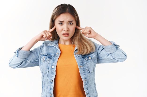 Nieśmiały niewinny zdenerwowany azjatycki blond dziewczyna nie może znieść ludzi walczących krzyczących marszczących brwi nerwowo patrzeć aparat zamknięty uszy niechętnie słyszeć głośny hałaśliwy imprezowa muzyka stojąca biała ściana zakłócona