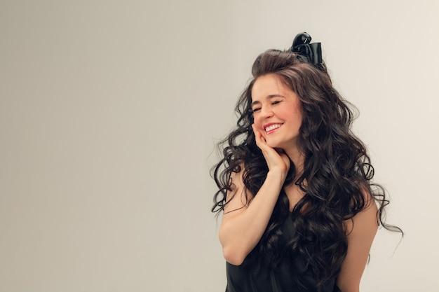 Nieśmiały Uśmiechnięty. Portret Pięknej Młodej Kobiety Na Szarym Studio Darmowe Zdjęcia