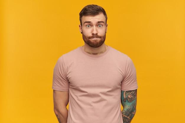 Nieśmiały, zawstydzony, wytatuowany młody brodaty mężczyzna w różowej koszulce trzyma ręce za sobą i wygląda nieśmiało na żółtej ścianie