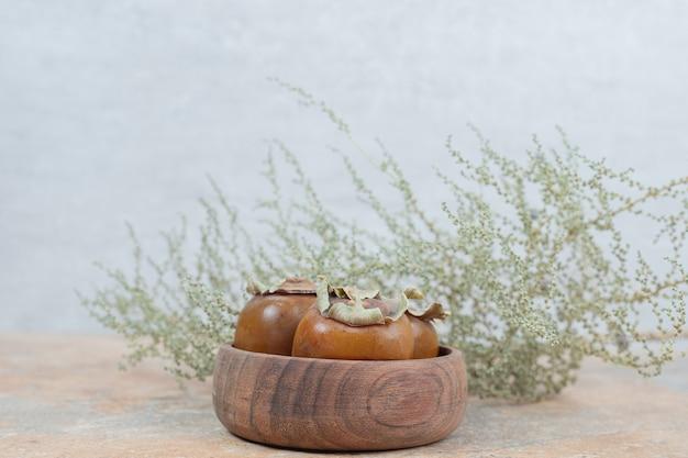 Niespieszne owoce w misce z trawą na marmurowym stole.