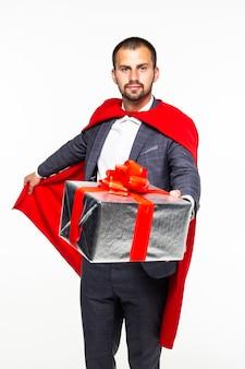 Niespodzianka biznesmen ubrany jak superbohater trzymając prezenty na białym tle