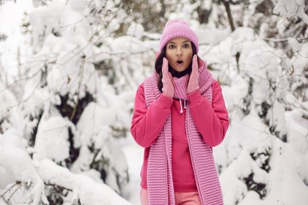 Niespodzianka dla kobiety w różowym ubraniu kurtka, szalik z dzianiny i czapka stoi zimą w zaśnieżonym lesie