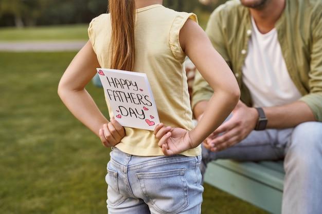 Niespodzianka dla taty małej dziewczynki ukrywającej ręcznie robioną pocztówkę dla ojca i córki