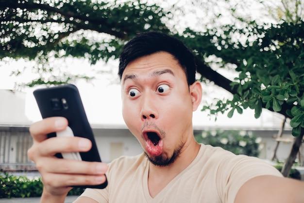 Niespodzianka i szok twarz człowieka spojrzeć na jego smartphone.