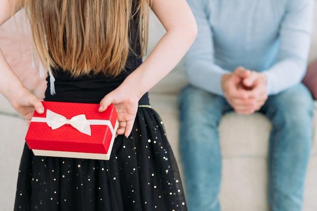 Niespodzianka prezent na dzień ojca od dziecka. prezent w nagrodę dla ukochanego tatusia. troskliwa i wdzięczna córka trzymająca za plecami świąteczną, zapakowaną paczkę w czerwonym pudełku.