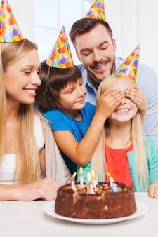 Niespodzianka! szczęśliwa czteroosobowa rodzina świętuje urodziny szczęśliwej małej dziewczynki siedzącej przy stole, podczas gdy jej brat zakrywa jej oczy rękami i uśmiecha się