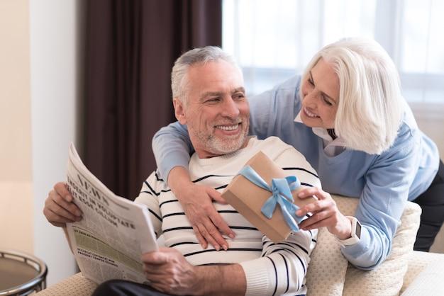 Niespodzianka. wesoła uśmiechnięta starsza kobieta daje prezent swojemu mężowi, stojąc obok sofy i wyrażając szczęście