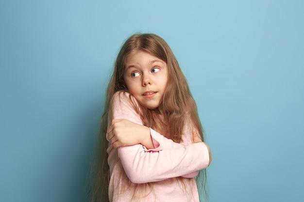 Niespodzianka. zdziwiona dziewczyna nastolatka na niebieskim tle studia. wyraz twarzy i koncepcja emocji ludzi. modne kolory. przedni widok. portret do połowy długości