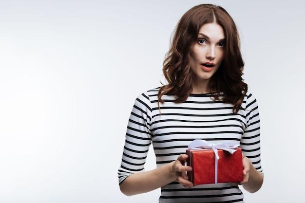 Niespodziewana niespodzianka. cudowna kasztanowowłosa młoda kobieta trzymająca pudełko z prezentem i wyglądająca na zaskoczoną, że go otrzymała